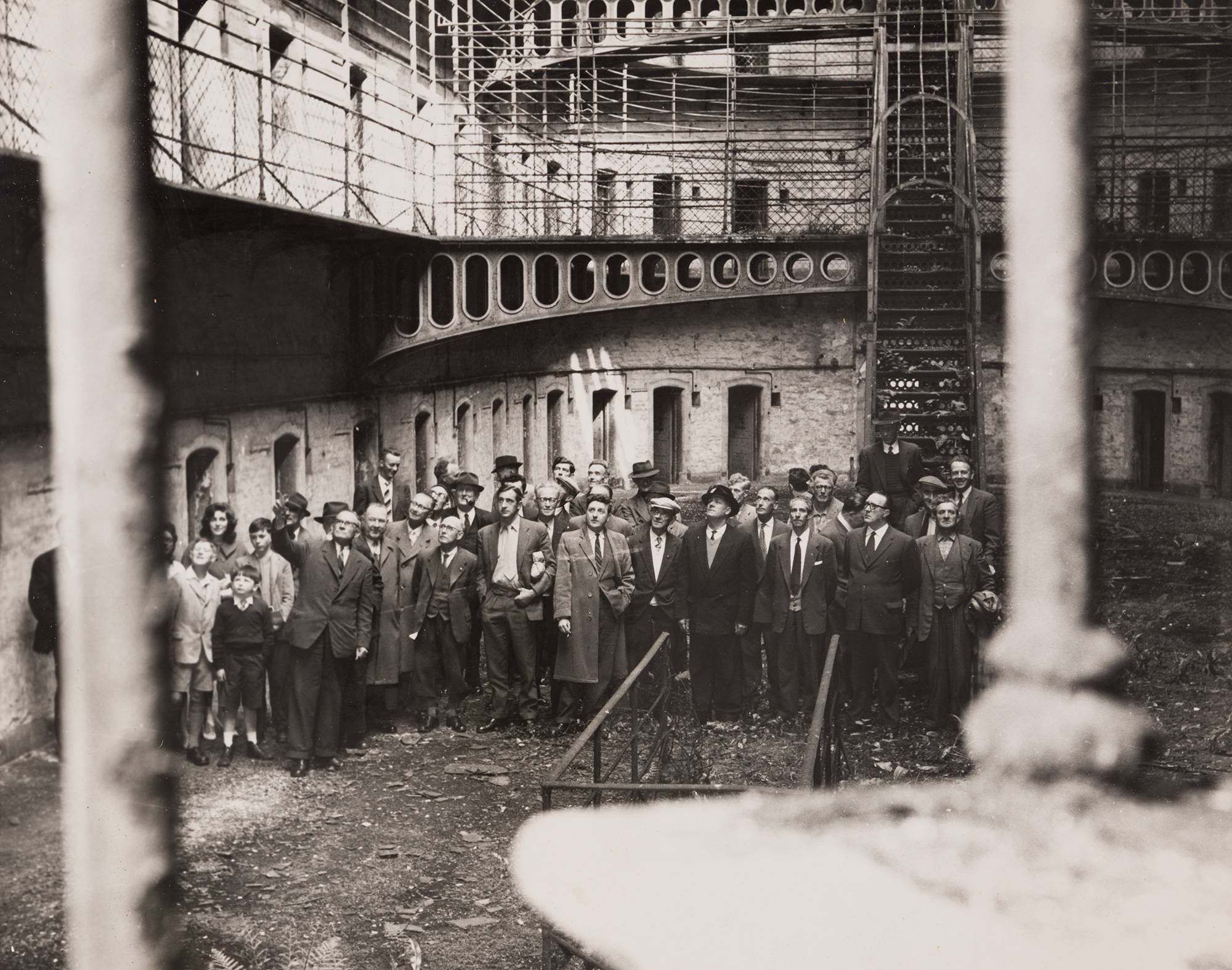 James Brennan, Secretary of the Kilmainham Jail Restoration Society, guides a group of visitors through the East Wing of the Jail, May 1960. OPW.